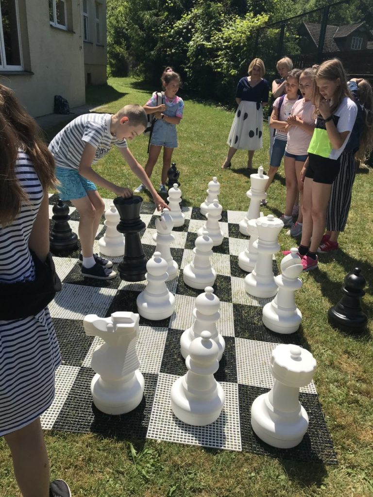 Uczestnicy Szach-Mat z biblioteką grający szachami ogrodowymi przed budynkiem biblioteki w Kamionce Wielkiej.