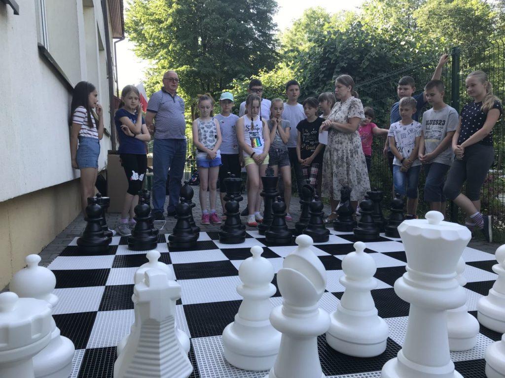 Uczestnicy Szach-Mat z biblioteką grający szachami ogrodowymi przed budynkiem filii biblioteki w Kamionce Wielkiej.