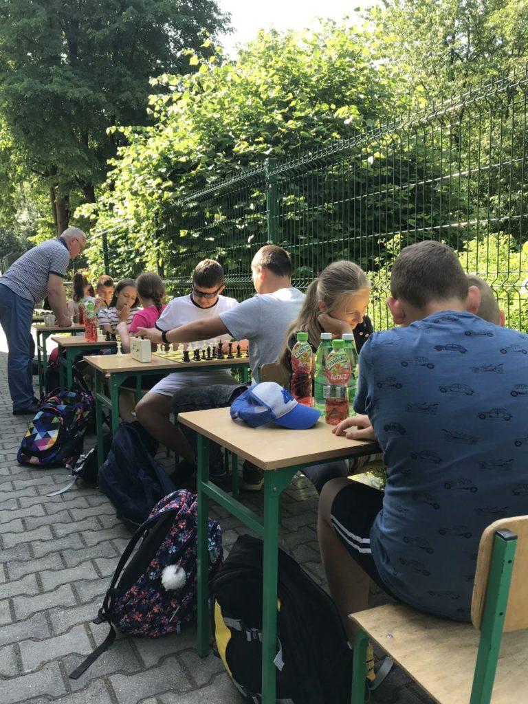 Uczesnicy turnieju szachowego Myśl i graj przed budynkiem filii biblioteki w Kamionce Wielkiej.