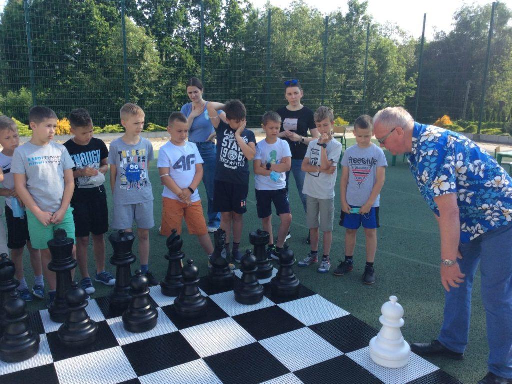 Grupa uczestników grająca szachami ogrodowy w Mystkowie.