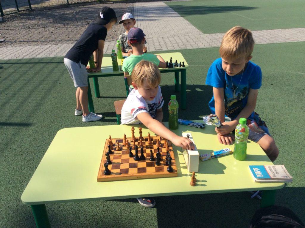 Uczestnicy Szach-Mat z biblioteką grający w szachy w Mystkowie.