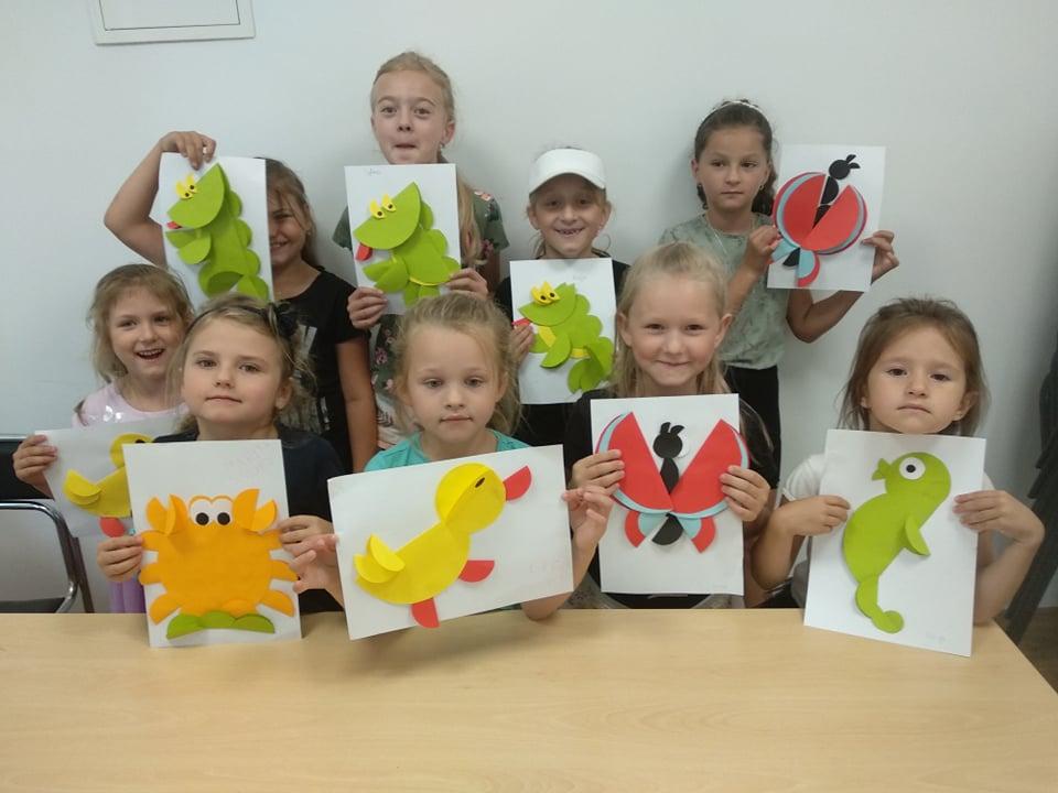 9 uczestników wakacji ze swoimi pracami plastycznymi w czytelni filii bibliotecznej w Mystkowie. Papierowe kaczuszki, dinozaury, kraby i koniki morskie.