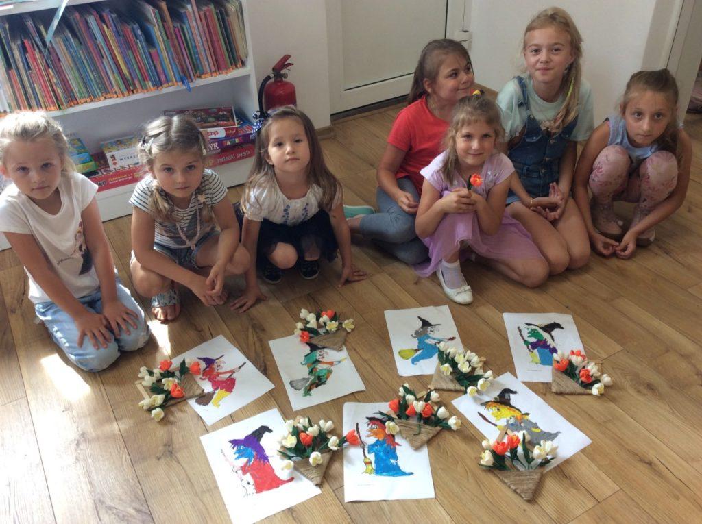 7 uczestników wakacji ze swoimi pracami plastycznymi w wypożyczalni filii bibliotecznej w Mystkowie. Plastelinowe kolorowanki Baby Jagi oraz koszyczki z krepinowych kwiatów.