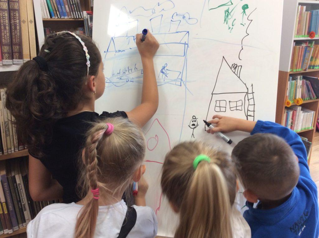 """Uczestnicy wakacji podczas zabawy w """"Wisielca"""", para uczetników maluje na flipcharcie."""