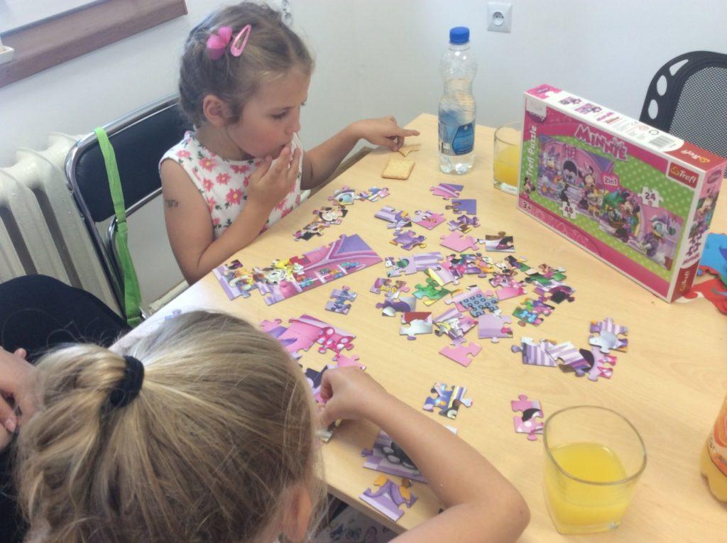 Uczestnicy wakacji układający puzzle w czytelni filii bibliotecznej w Mystkowie.