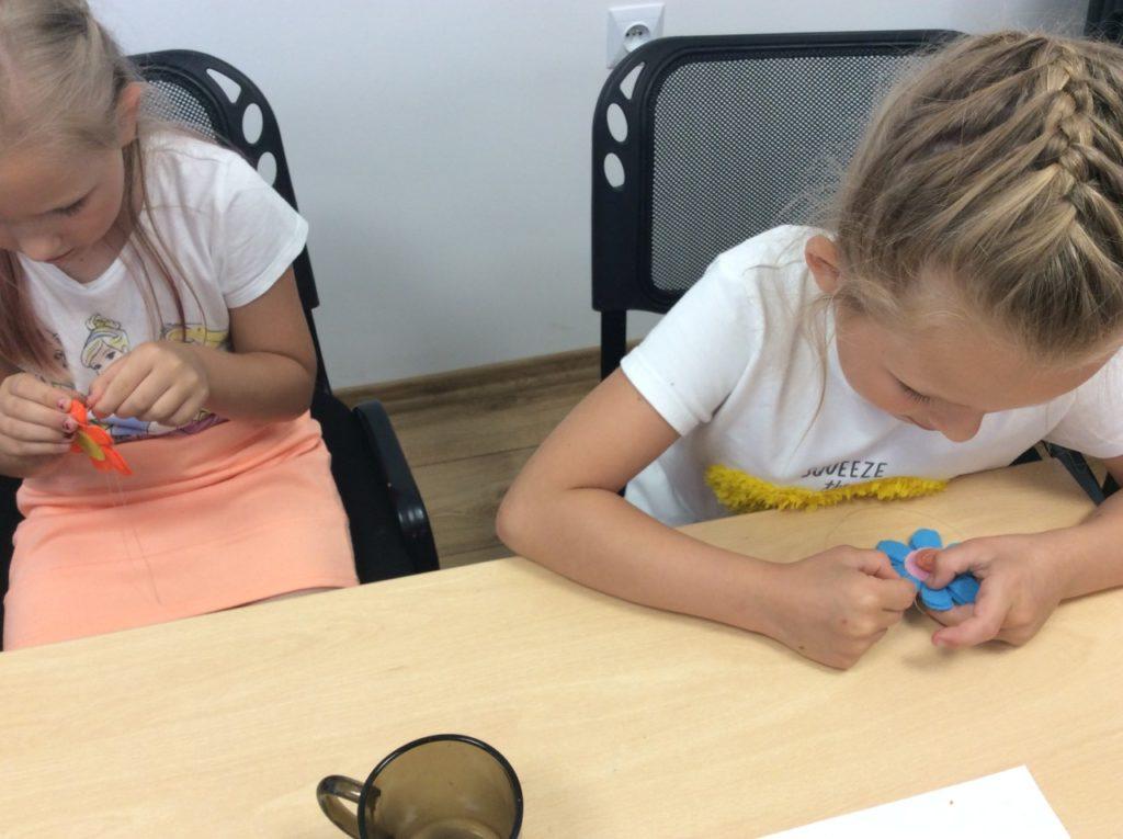 Uczestnicy wakacji szyjący filcowe bryloczki do kluczy w czytelni filii bibliotecznej w Mystkowie.
