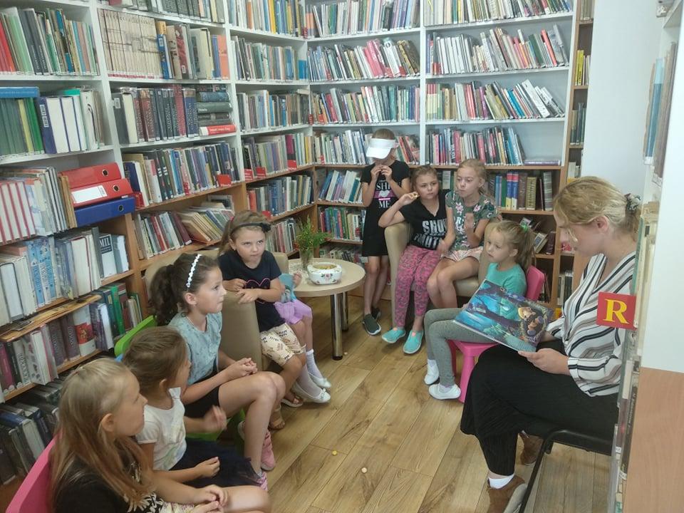 Głośne czytanie podczas wakacji w wypożyczalni filii bibliotecznej w Mystkowie.