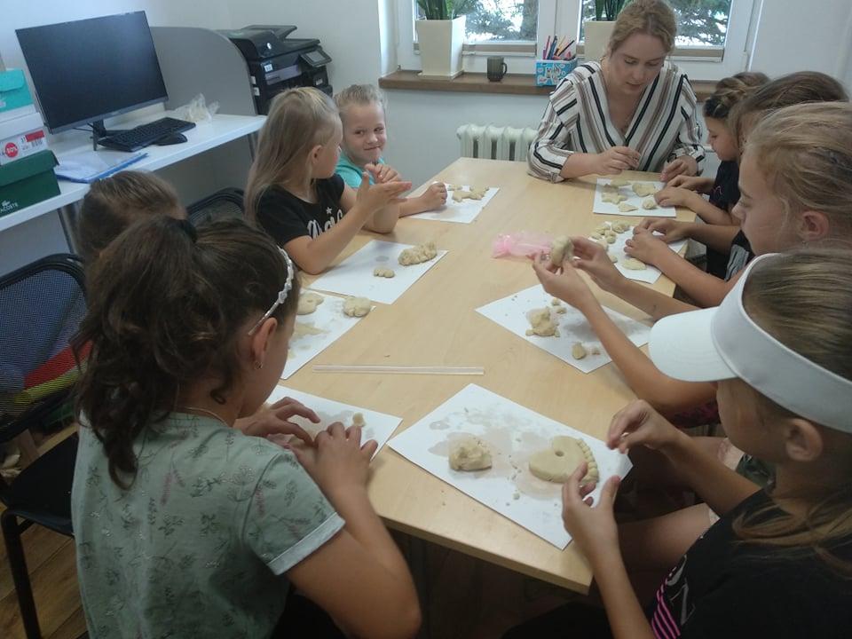 Uczestnicy wakacji wykonują prace z ciasta solnego w czytelni filii bibliotecznej w Mystkowie.