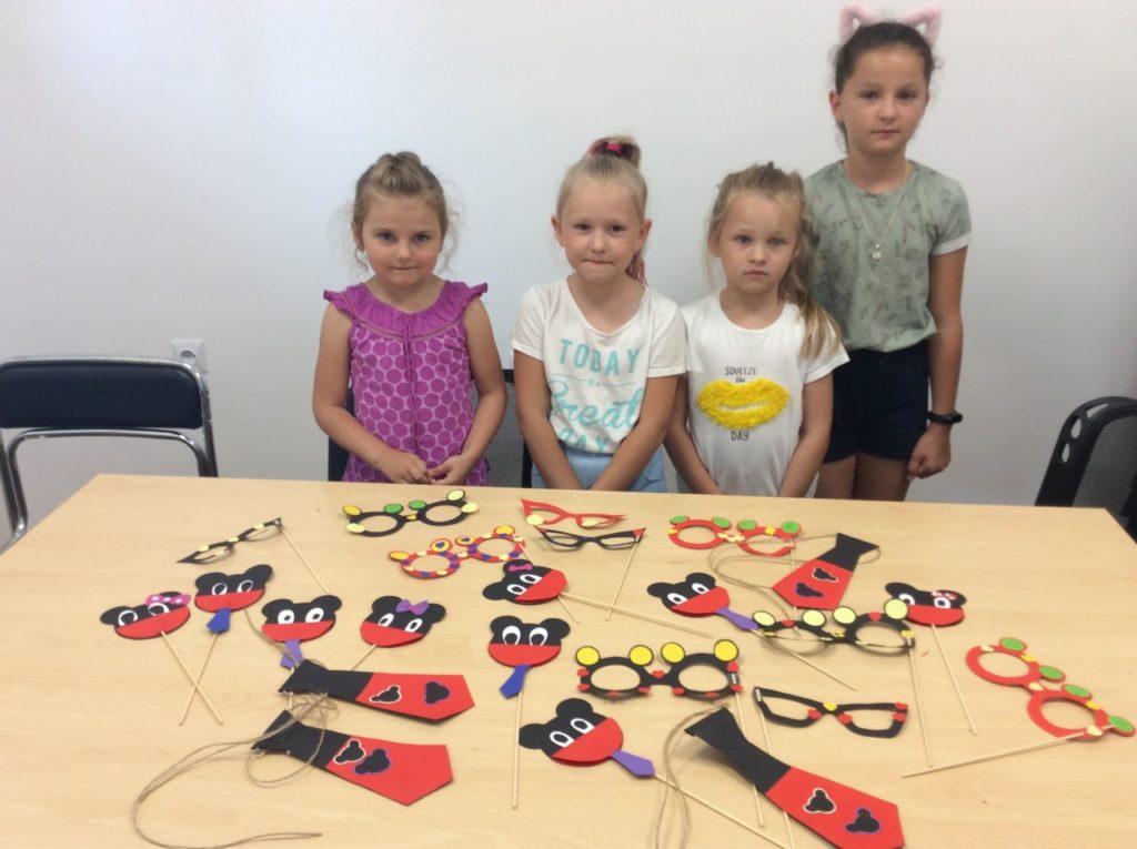4 uczestników wakacji ze swoimi pracami plastycznymi w czytelni filii bibliotecznej w Mystkowie. Papierowe Myszki Miki i okulary z motywem Myszki na drewnianych patyczkach oraz papierowe krawaty z Myszką Miki.