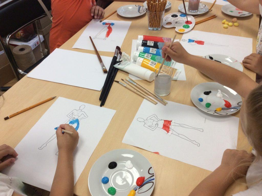 Uczestnicy wakacji podczas pracy plastycznej, wykorzystujący farby akrylowe do projektowanie własnych ubiórów.
