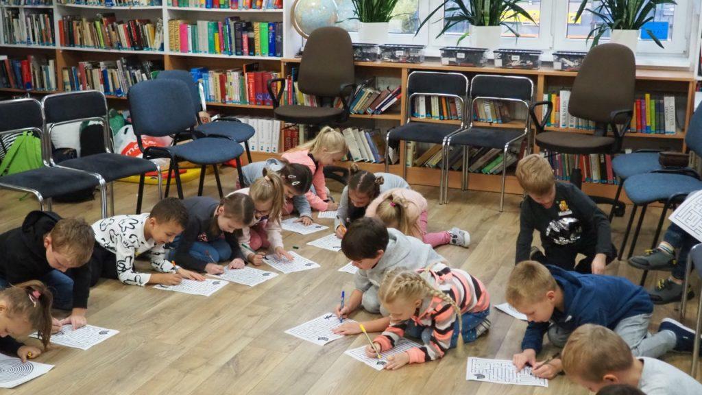 Uczestnicy Nocy Bibliotek rozwiązujący zagadki w czytelni biblioteki.