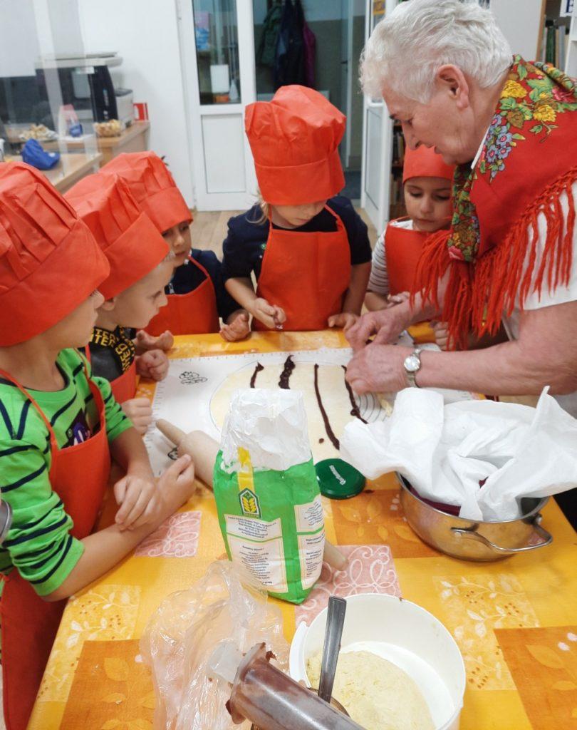 Dzieci uczestniczące w warsztatach kulinarnych.