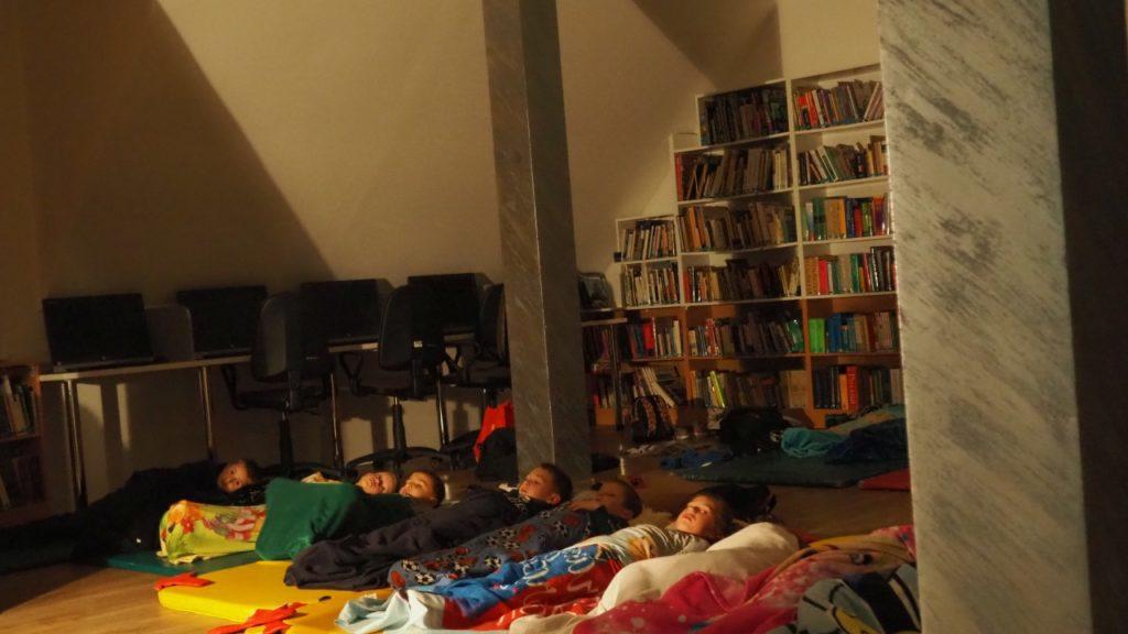 Dzieci leżąc pod kocami i śpiworami, słuchają bajki.