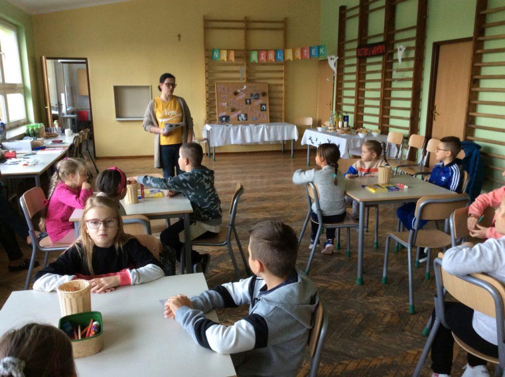 Sala gimanstyczna w szkole podstawowej w Mystkowie. Organizator wita dzieci na akcji Noc Bibliotek.