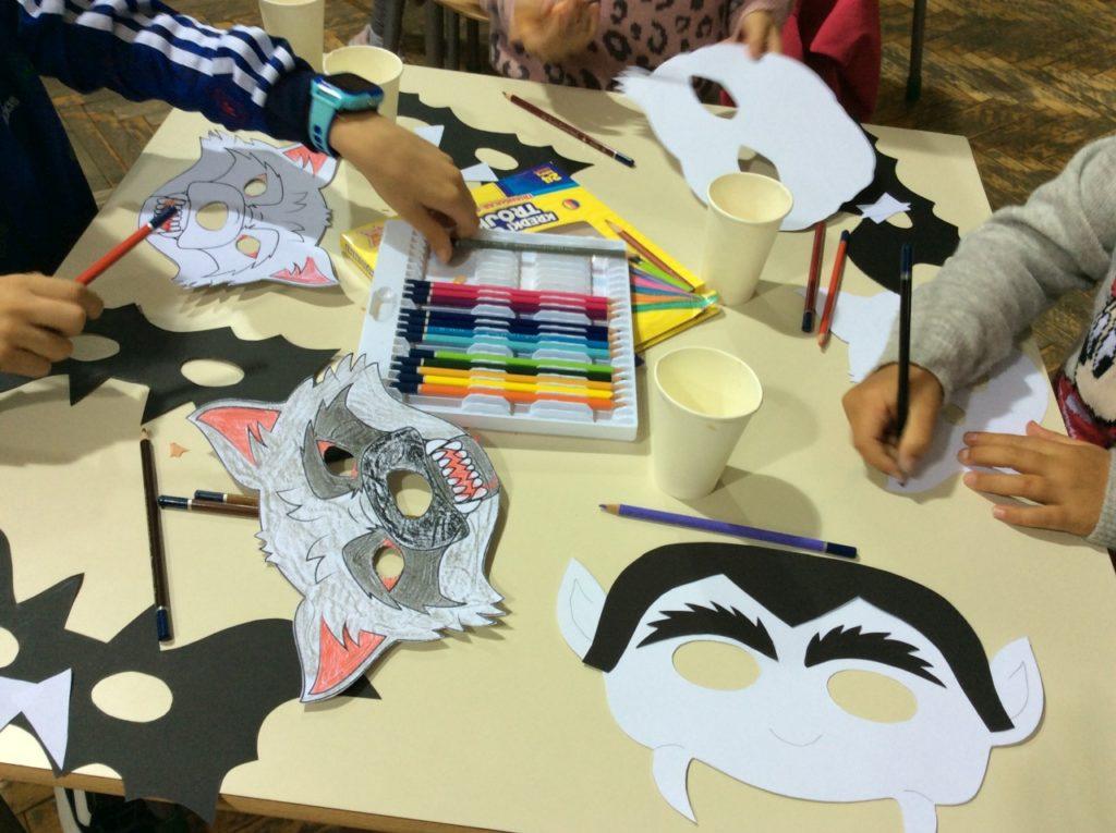 Dzieci wykonujące maski wilkołaków, wampirów i potworów.