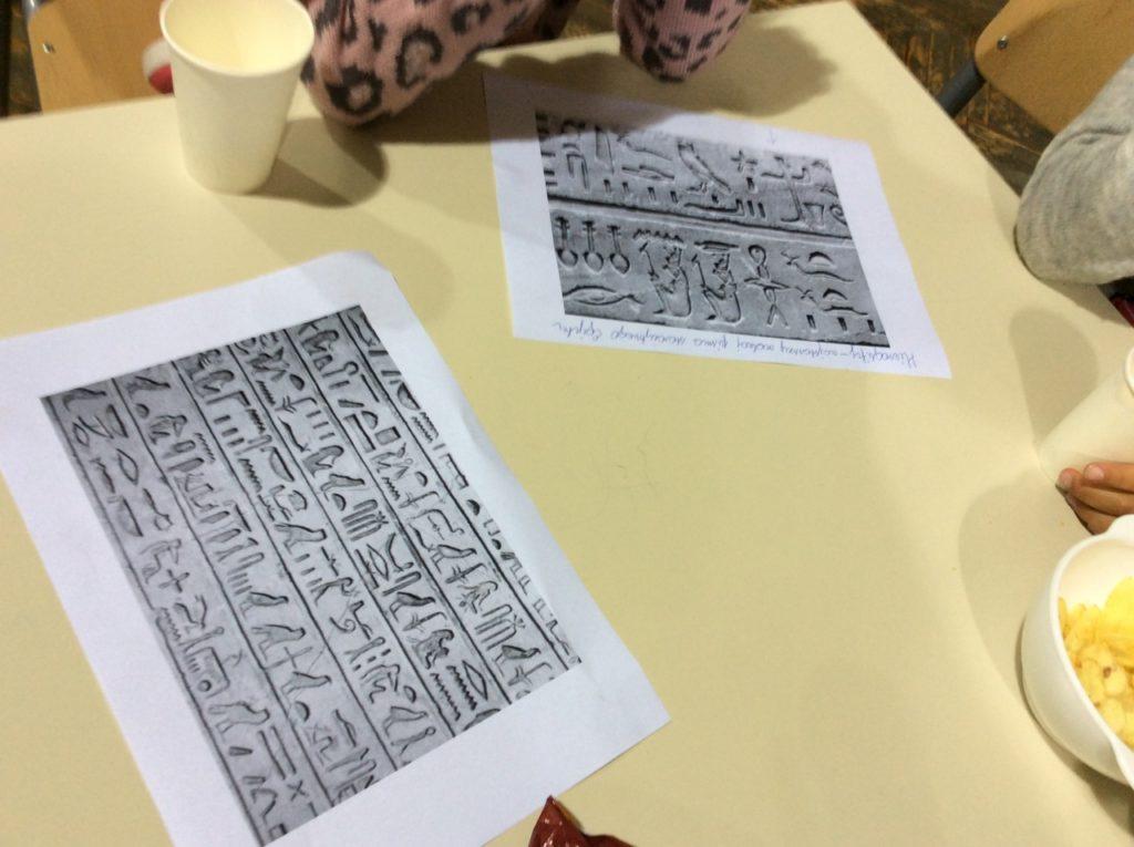 Hieroglify i portrety w stylu egipskim.