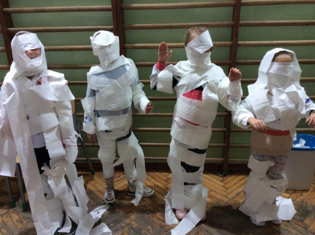 Czterech uczestników jako mumie, które powstały w zadaniu sprawnościowym z papierem toaletowym.