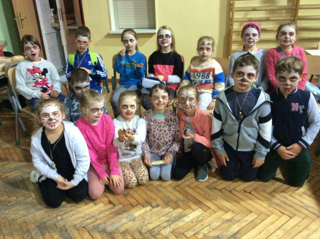 Grupowe ujęcię uczestników, którzych twarze z pomocą makijażu zamieniły się w czarownice, wampiry i duchy.