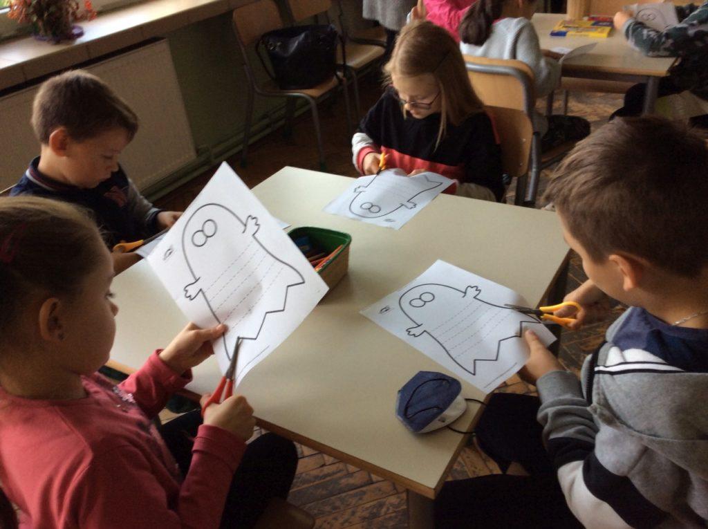 Dzieci wycinają z papierowych kartek duszki.